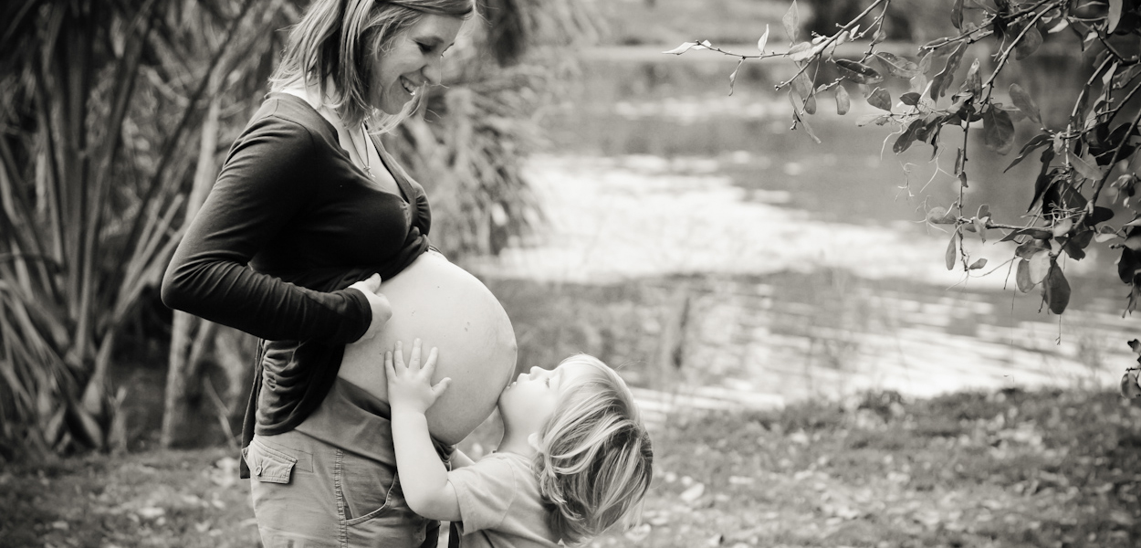 Pregnant mom and daughter in city park.