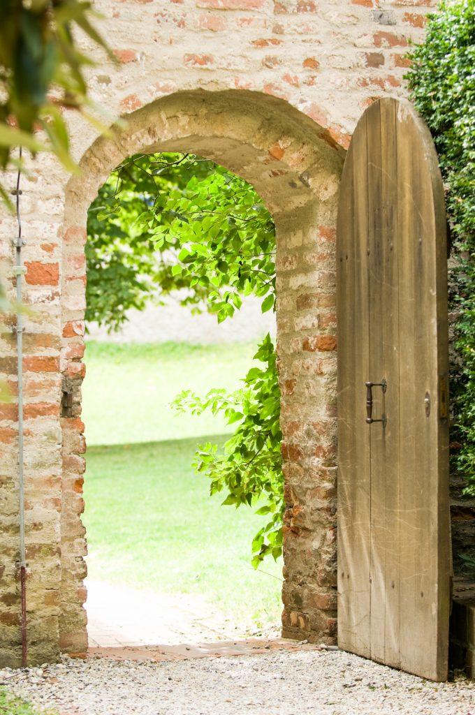 Rustic brick garden door arch exterior with green foliage